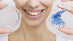 Woman with a healthy smile holding retainer and aligner